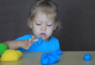 little girl playing with colorful play dough