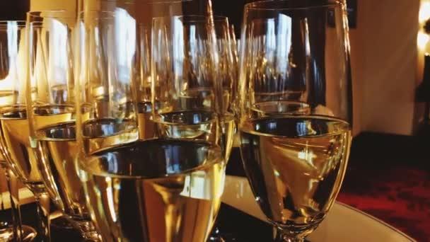 Sklenice šampaňského a bílého šumivého vína ve zlatém svátečním světle na slavnostní akci, luxusní svatbě a slavnostním otevření