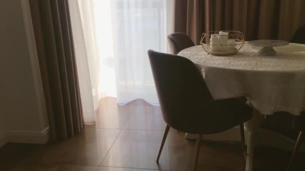Pohled na jídelnu, kulatý stůl, židle a okna zdobené závěsy, nábytek a luxusní design interiéru