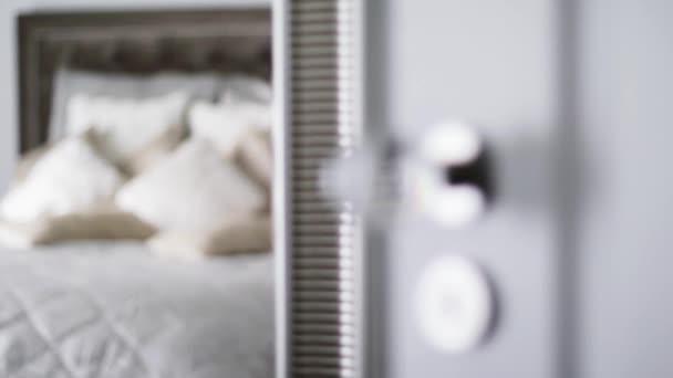 Dekorativní polštáře a polštáře na posteli v luxusním ložnicovém interiéru, otevřené dveře do pokoje, domácí výzdoba a design
