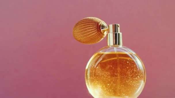 Luxury golden perfume bottle and shining light flares on pink background, glamorous fragrance scent as perfumery product for cosmetic and beauty brand