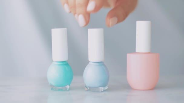 Dámské ruce a láhve na nehty, organický kosmetický přípravek pro francouzskou manikúru, barevný pastelový lak na nehty na mramorovém stole, dámský make-up a kosmetická značka