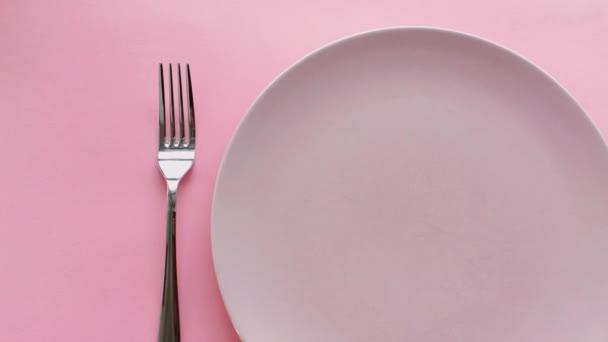 Růžový stůl s pivoňkovými květy na talíři a příbory pro luxusní večeři, svatbu nebo oslavu narozenin