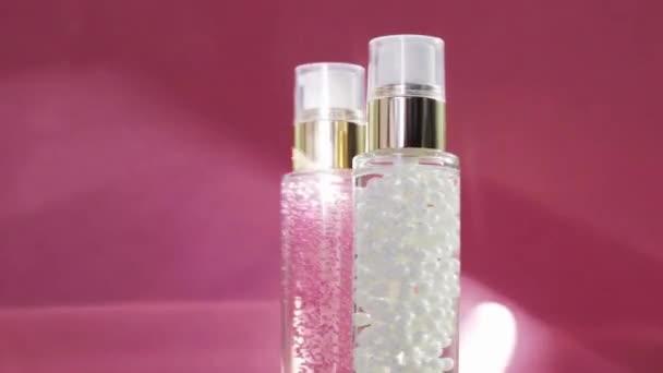 Luxusní výrobky pro péči o pleť a lesklé světelné erupce na růžovém pozadí, make-up a sérový gel jako péče o pleť rutina pro kosmetiku a kosmetiku obličeje značky