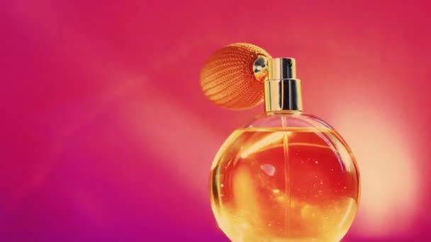 Golden fragrance bottle and shining light flares on pink background, glamorous perfume scent as holiday perfumery product for cosmetic and beauty brand