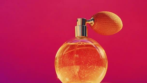 Goldene Duftflasche und leuchtende Lichterketten auf rosa Hintergrund, glamouröser Parfümduft als Urlaubsparfümerieprodukt für Kosmetik- und Schönheitsmarken