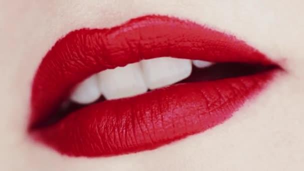 Lippen mit rotem Lippenstift und weißen Zähnen, die lächeln, Makro-Nahaufnahme eines glücklichen weiblichen Lächelns, Zahngesundheit und Beauty-Make-up