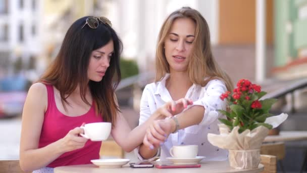 Two beautiful young women sit at the table in cafe and talking. 4k. slow motion
