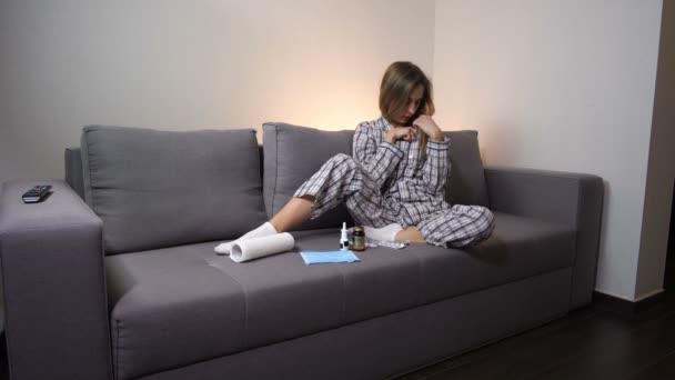 krankes Mädchen im Schlafanzug zu Hause. Blick auf das Thermometer. Sie hat Fieber. 4k langsam mo