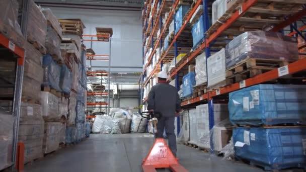 Egy férfi egy logisztikai raktárban egy raklap felvonót hordoz. 4k lassú Mo