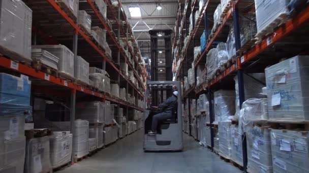 Camera movement between the racks with the goods. Ahead is a man on a forklift. 4K Slow Mo