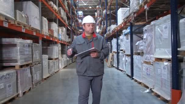 A Raktári munkás egységes sétál az állványon, ő rendelkezik egy mappát a kezében, ő teszi jegyzetek. 4k lassú Mo