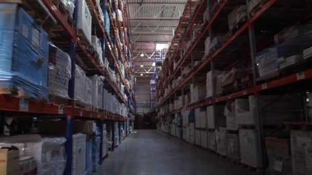 Panoráma a logisztikai raktárról. A folyosón a kamera mellett a magas sorok az árut. 4k lassú Mo