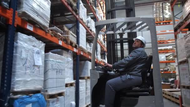 Warehouse worker riding a forklift along the pallet with the goods. 4K Slow Mo