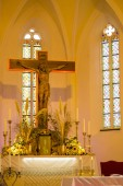 Photo Inside of church in Slovakia featuring stained glass windows, candles and cross.