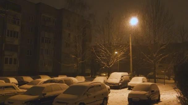 Starker Schneefall bedeckt die nachts auf dem Parkplatz abgestellten Autos