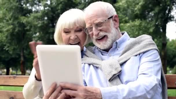 šťastný pár vysokých používání tabletu a mává rukama během volání videa v parku