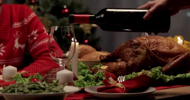 cropped view of wife pouring wine into glass, baked turkey on dinner table on Thanksgiving Day