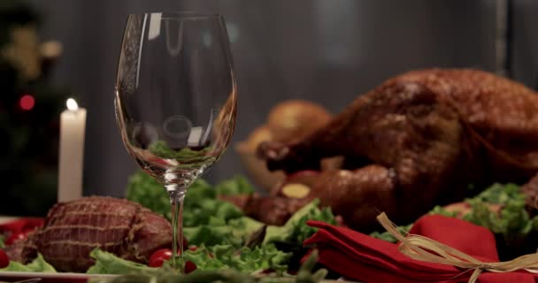 cropped view of woman pouring red wine into glass, baked turkey on dinner table on Thanksgiving Day