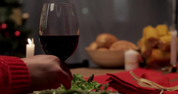 cropped view of husband taking glass of wine while wife putting baked turkey on festive table on Thanksgiving Day