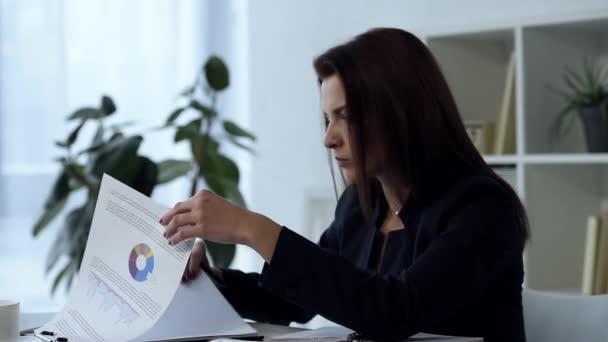 jistý dospělý podnikatelka pracující s doklady u stolu v moderní kanceláři