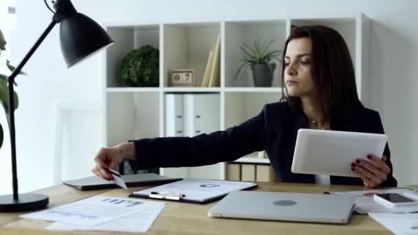 Üzletasszony hitelkártyával, csinál online vásárlás a digitális tábla asztalnál hivatalban