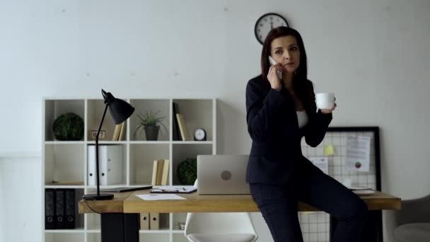 joyful businesswoman drinking coffee and talking on smartphone near table in office