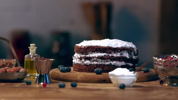 lassú mozgás, női szakács szórás bogyók a torta a összetevők-fa tábla