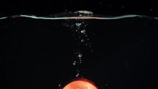 bright red apple falling into clear water on black background