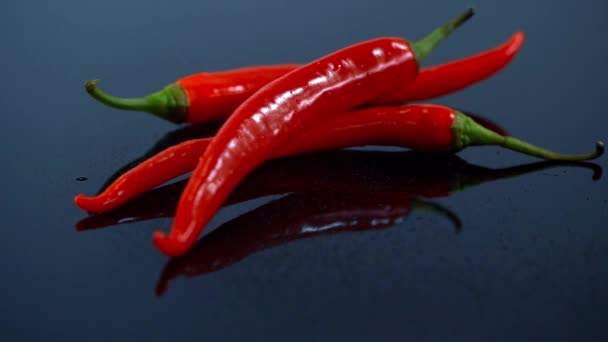 Studio pro natáčení vody postřik na červené chilli papričky na tmavý povrch, kapky a reflexe