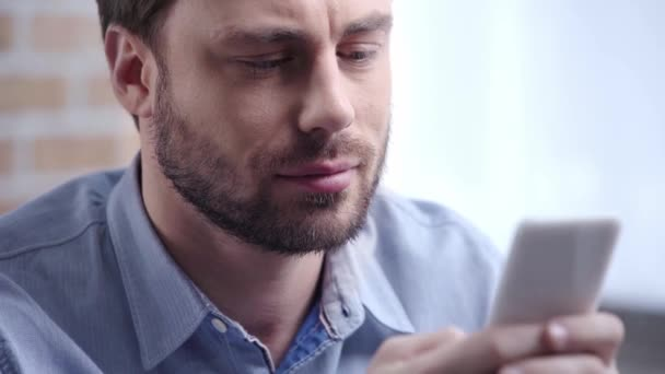 Handsome businessman in blue shirt with beard blinking while typing on smartphone