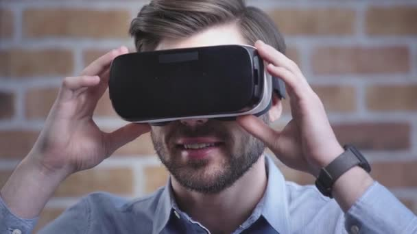 Smiling man with wristwatch wearing vr headset, looking around and stretching out hand