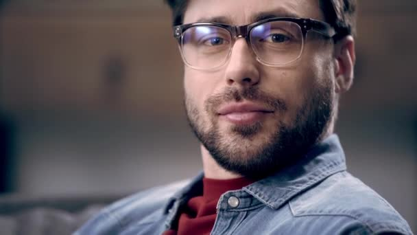 Handsome young man in glasses turning at camera and starting to laugh at home
