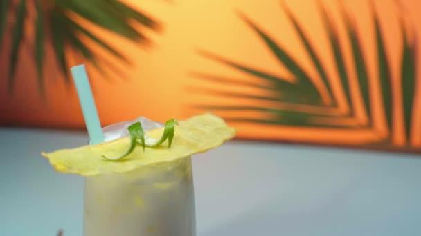 zár-megjelöl kilátás a pina colada koktéllal vizes pohár-forog a narancssárga háttérben zöld pálmalevél díszítéssel