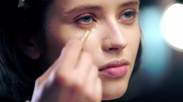 cropped view of makeup artist applying concealer under eye on model face with cosmetic brush