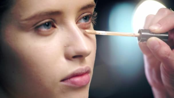 selective focus of makeup artist applying concealer under eye on model face with cosmetic brush
