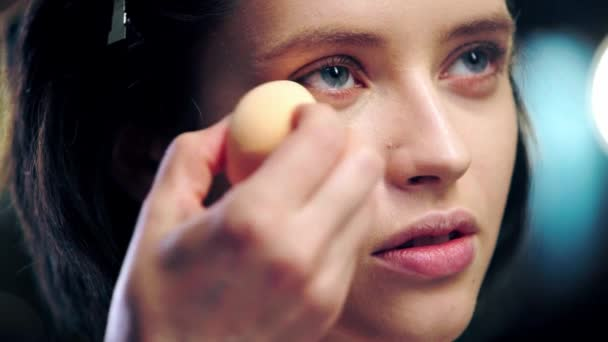 cropped view of makeup artist applying concealer under eye on model face with cosmetic sponge