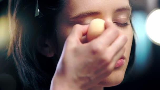 oříznutý pohled na make-líčka, který se ukrývá v okolí očí na modelovém obličeji s kosmetickou houbou