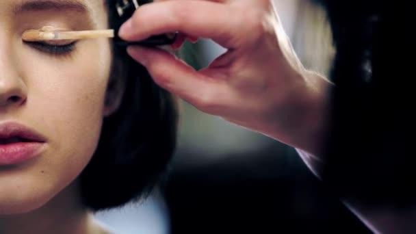 oříznutý pohled na make-up výtvarník s kosmetickým kartáčkem na model víčka