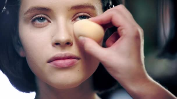 cropped view of makeup artist applying concealer under model eye with cosmetic sponge