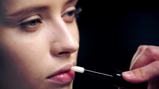 partial view of makeup artist applying shiny lip gloss on model lips with cosmetic brush isolated on black