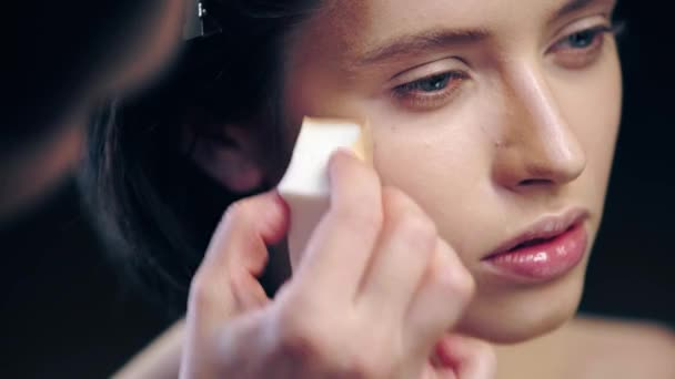 cropped view of makeup artist shading contouring on model face with cosmetic sponge isolated on black
