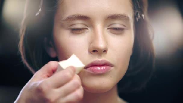 oříznutý pohled na líčidla stínování na modelový obličej s kosmetickou houbou