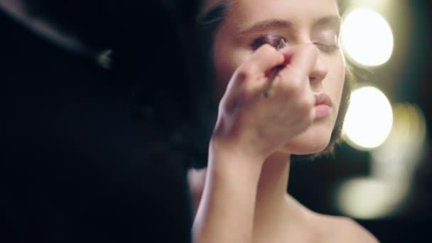 oříznutý pohled na líčidla aplikování a stínování tekutého hnědého oka na modelu víčka