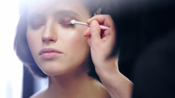 selektivní zaměření naladěného umělce stínování tekuté hnědé oči stín na víko modelu s kosmetickým kartáčkem