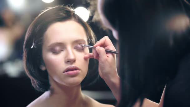 selective focus of makeup artist applying liquid brown eye shadow on model eyelid with cosmetic brush