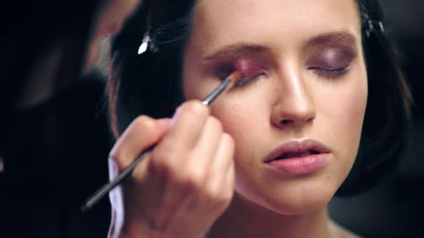 cropped view of makeup artist shading brown eye shadow with cosmetic brush