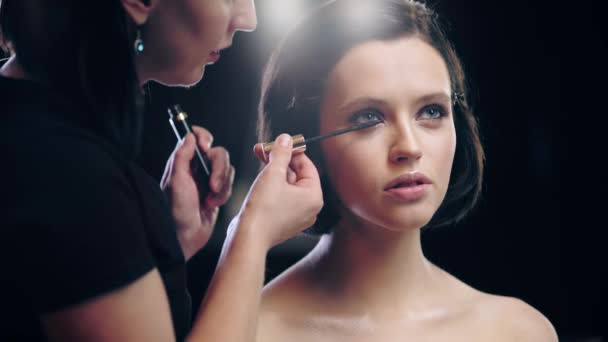 cropped view of makeup artist applying mascara on model eyelashes with cosmetic brush