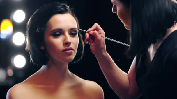 makeup artist applying eyebrow shades with cosmetic brush