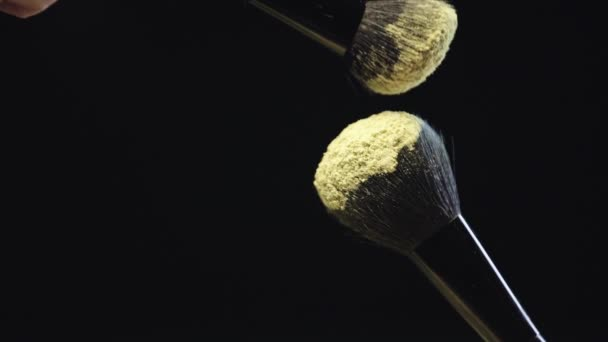 slow motion shoot of two cosmetic brushes touching and scattering yellow holi paint